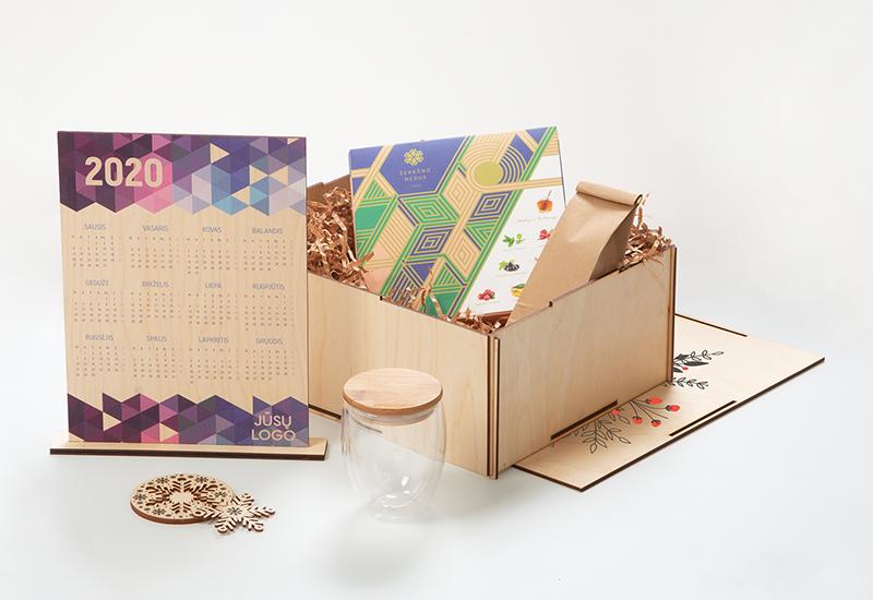 Kalėdinės dovanų idėjos verslui, medinis kalendorius, padėkliukas su snaige, stiklinis puodelis, medus, arbata, faneros dėžė su spauda